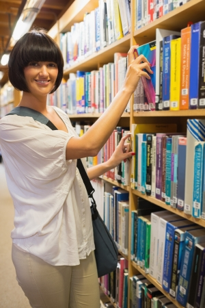 Black-haired woman taking a book out of the shelves in the library Stock Photo - 15593392