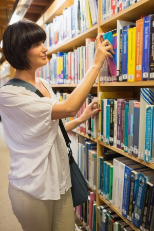 Woman choosing a book from the shelves in the library Stock Photo - 15593436
