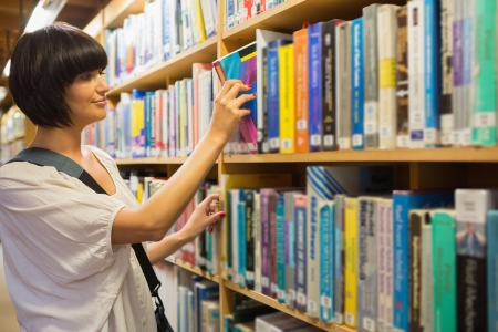 Woman pulling out a book from a shelf in the library Stock Photo - 15593396