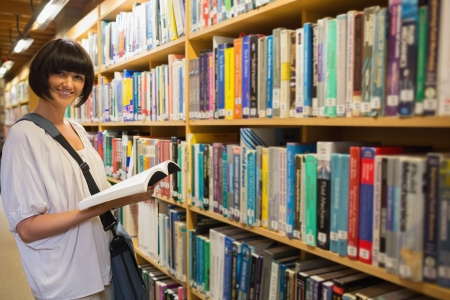 Woman holding a book next to a shelf in the library Stock Photo - 15593494