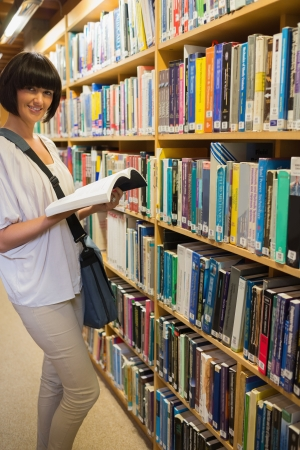 Woman reading a book in the library and smiling Stock Photo - 15584327