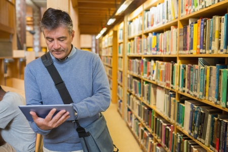 educational research: Man holding a tablet pc amongst shelves in a library