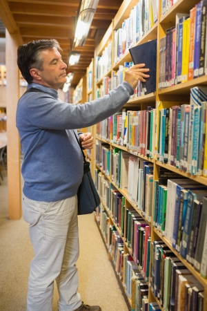 Man taking a book from the shelves in the library photo