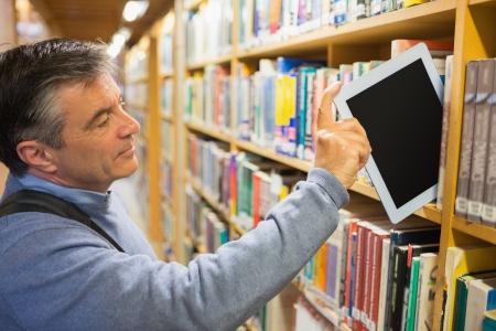 pile of books: Man taking a tablet pc from the shelves in a library