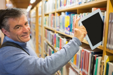 Smiling man taking a tablet pc from the shelves in library photo