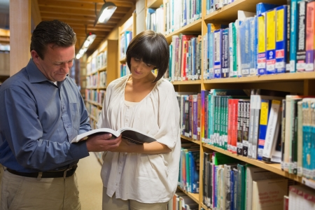 Man and woman looking at book in the library photo