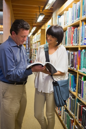 Woman and man reading together in the library Stock Photo - 15584107
