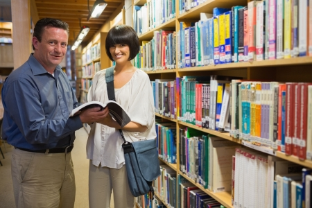 Man showing woman book standing in library Stock Photo - 15584334