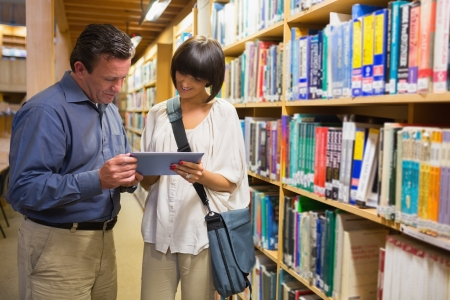 Man and woman looking at tablet pc in the library photo