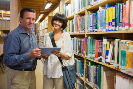 Man and woman standing happily in the library while holding a tablet computer photo