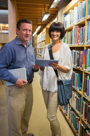 Man holding book standing next to woman using tablet pc in the library photo