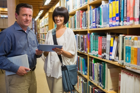 Woman and man holding tablet pc standing in library photo