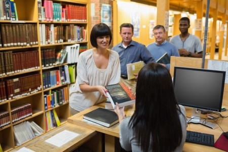 Librarian handing book to woman at library desk Stock Photo - 15584318
