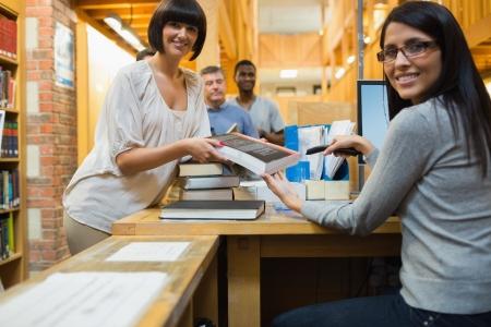 codigos de barra: Bibliotecario de escaneo de libros y la entrega a la mujer en el mostrador de la biblioteca Foto de archivo