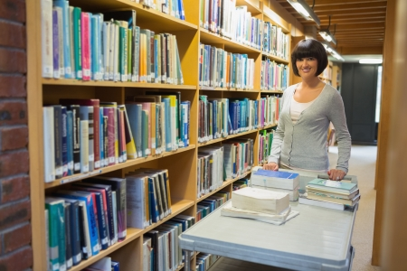Librarian putting books back on shelf photo