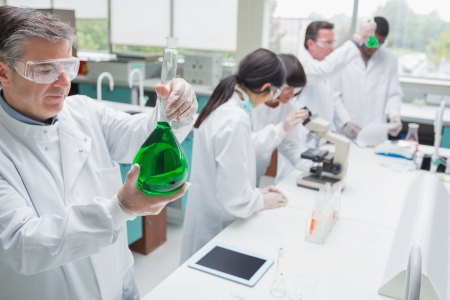 Chemists working in a laboratory and viewing the green liquid photo