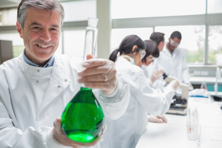 Chemist smiling and holding beaker of green liquid in lab photo