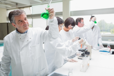 Chemists doing research on green liquid in the laboratory photo
