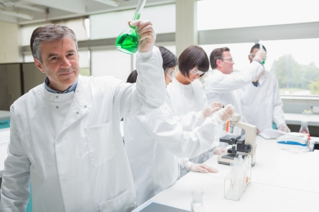 Chemist raising beaker of green liquid in busy lab photo