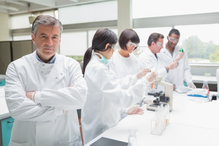 clinical: Chemist standing with arms folded in busy lab