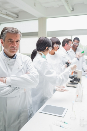 Chemist standing in front of tablet pc in busy lab photo