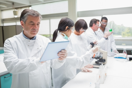 laboratory glass: Chemist using tablet pc in busy lab