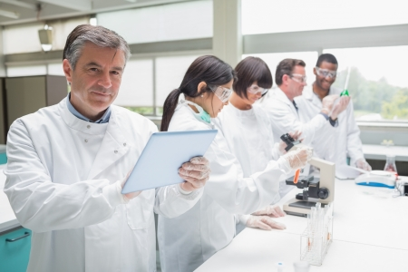 scientists: Smiling chemist using tablet pc in busy lab