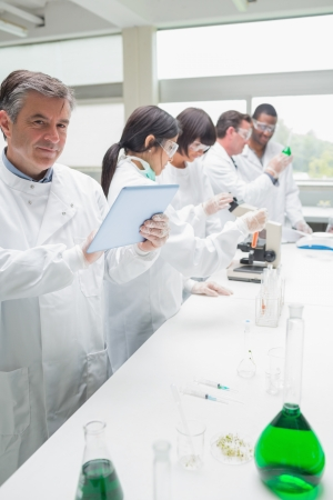 Happy chemist using tablet pc in busy lab photo