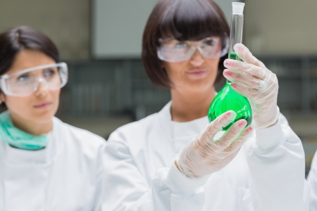 Female chemists viewing t green liquid in the laboratory photo