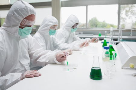 Three chemists working in protective suits in the laboratory photo