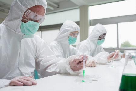 Chemists in protective suits working in the laboratory photo