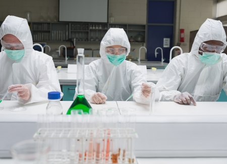Chemists working in protective suits in the lab photo