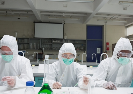 Chemists in protective suits adding liquid to petri dishes in the lab photo