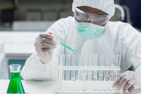 Chemist in protective suit filling test tubes with green liquid in the lab photo