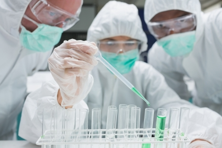 Chemist adding green liquid to test tubes as two others are watching in the lab photo