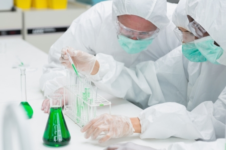Two chemists adding green liquid to test tubes in the lab photo