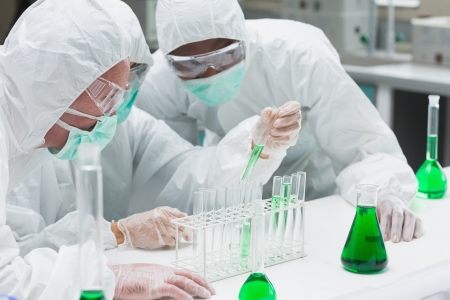 chemical substance: Two chemists experimenting with the green liquid in the laboratory