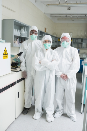 Team of chemists in protective suits standing in the lab photo