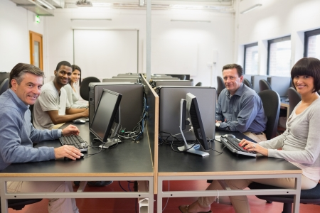 Happy  group in a computer room in college photo