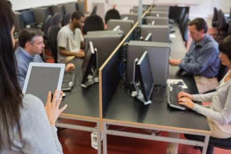 monitor de computadora: Mujer que sostiene una PC de la tableta mientras ense�a su clase de computaci�n
