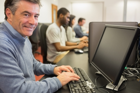 looking at computer screen: Smiling man sitting in front of the computer in class