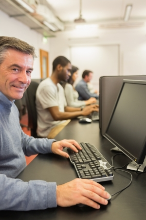 Smiling man working with the computer in class Stock Photo - 15593487