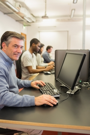 Cheerful man using the computer while working in a class Stock Photo - 15593468