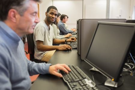 Man looking up from computer class in college photo