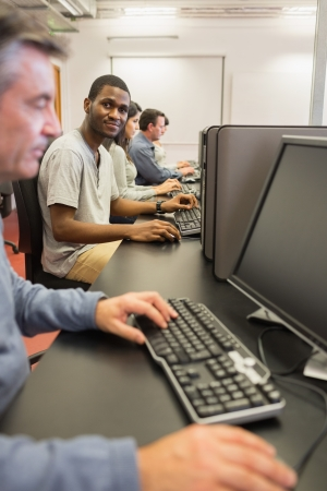 Smiling young man at computer class in college Stock Photo - 15584958