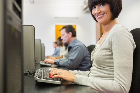 Smiling woman in the row of the computer class working Stock Photo - 15592580