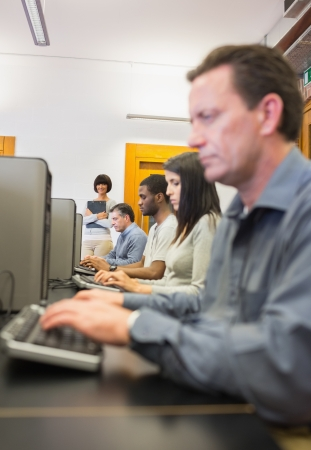 Teacher smiling while others working in computer class photo
