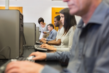 Teacher helping her students in computer class in college Stock Photo - 15592549