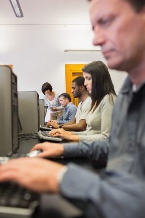 Woman helping her student with the computer in computer class Stock Photo - 15593318