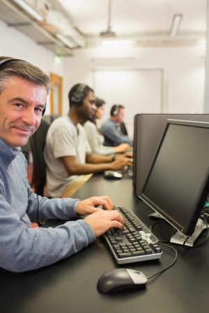 Smiling man in computer class in college photo